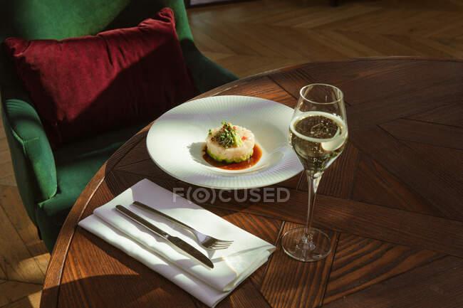 Закрийте погляд на смачну білу страву з овочами й келихом вина в ресторані. — стокове фото