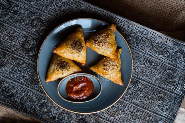 Vista dall'alto di panini triangolo gustosi freschi con semi e salsa sul piatto — Foto stock