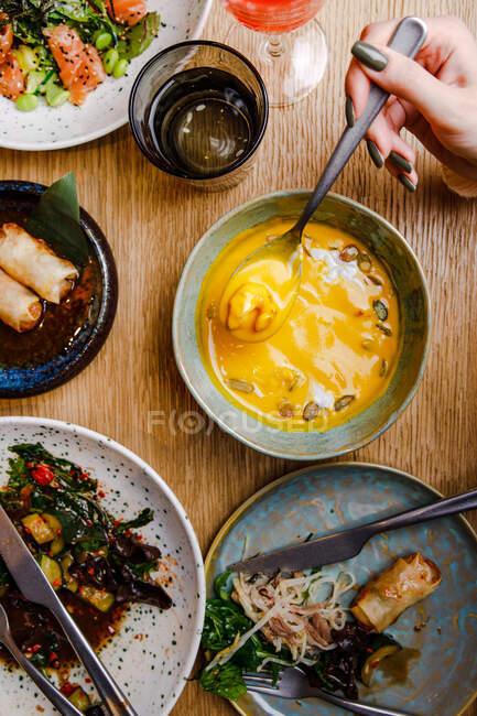 Vista superior de la mesa servida con varios platos y personas cenando en la mesa - foto de stock