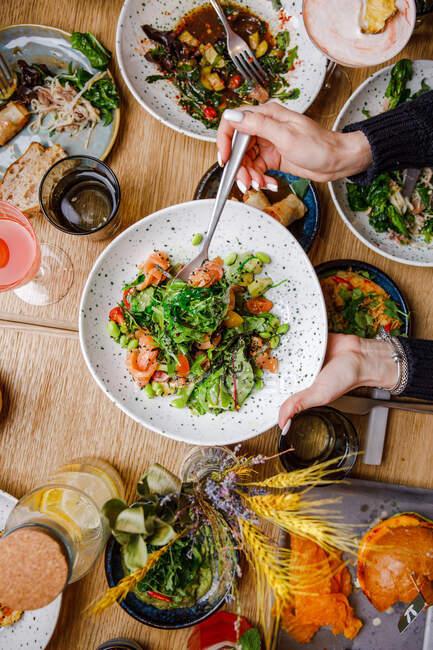 Верхний вид обслуживаемого стола с различными блюдами и люди обедают за столом — стоковое фото