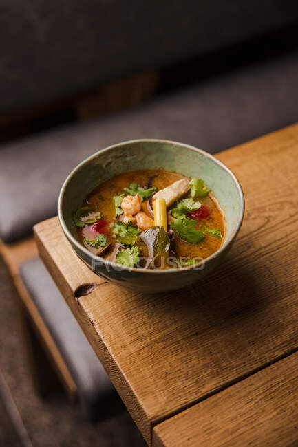 Soup with shrimps, vegetables, and pieces of fish on the table — Stock Photo