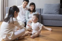 Chinese family sitting on wooden floor in living room — Stock Photo