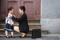 Китайский мать регулировочный дочь школьной формы на улице — стоковое фото