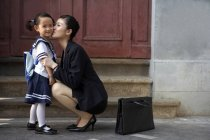 Chinese mother kissing schoolgirl on street — Stock Photo