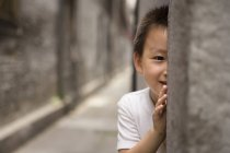 Chinese boy playing hide and seek — Stock Photo