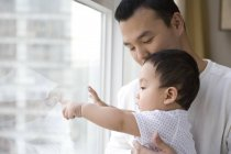 Chinese man with baby boy looking through window and pointing — Stock Photo