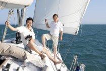 Jovens e idosos chineses navegando em iate — Fotografia de Stock