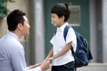 Chinese father and schoolboy holding hands on street — Stock Photo