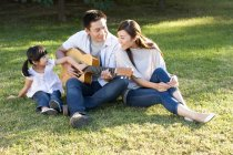 Chinese man playing guitar with family in park — Stock Photo
