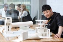 Chinesischer Architekt Zusammenarbeit mit Kollegen im Hintergrund — Stockfoto