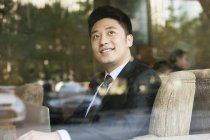 Chinese businessman looking through window in cafe — Stock Photo