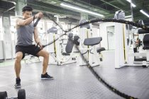 Asian man exercising with battling rope at gym — Stock Photo