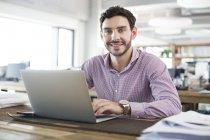 Di impiegato maschio che lavora con il computer portatile in ufficio — Foto stock