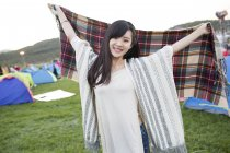 Mujer china sosteniendo bufanda en el festival de camping - foto de stock