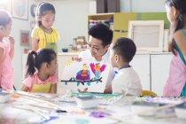 Китайські діти, дивлячись на картину в мистецтві клас з вчителем — стокове фото