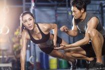 Китаянка работает с тренером в тренажерном зале — стоковое фото