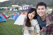 Coppia cinese avvolto nella coperta abbracciando presso camping festival — Foto stock
