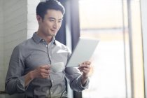 Asian man using digital tablet in office — Stock Photo
