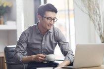 Азіатських людині, робота з ноутбук та каву в офісі — стокове фото