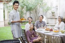 Chinese man holding grilled corn for multi-generation family in courtyard — Stock Photo
