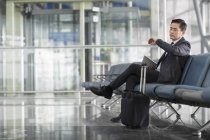 Asian man waiting in airport and looking at wristwatch — Stock Photo