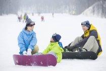 Parents chinois enseignement fils Snowboard — Photo de stock