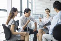 Китайская команда бизнесменов обсуждает работу на встрече — стоковое фото