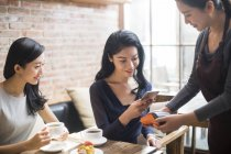 Chinese female friends paying with smartphone in coffee shop — Stock Photo