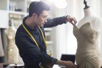 Male asian fashion designer working in studio — Stock Photo