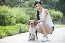 Молодая китаянка позирует с милым биглом в парке — стоковое фото