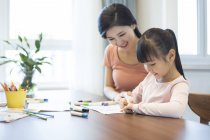 Китайський мати і дочка, спираючись на стіл — стокове фото