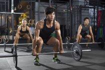Chinese athletes lifting barbells at gym — Stock Photo