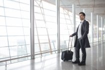 Asian man standing with wheeled luggage in airport lobby — Stock Photo
