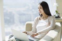 Mujer China con portátil en el sofá en casa interior - foto de stock