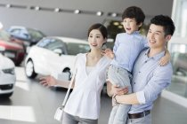 Chinese family in car dealership showroom — Stock Photo