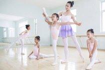 Chinese ballet instructor teaching girls in ballet studio — Stock Photo