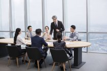 Chinese business team having meeting with foreign partners in board room — Stock Photo