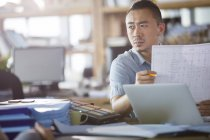 Male asian architect holding blueprint in office — Stock Photo