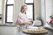 Старший Китайська жінка, що робить пельмені кухні — стокове фото