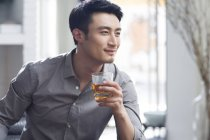 Asian man enjoying alcoholic drink — Stock Photo