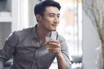 Homem asiático, apreciando a bebida alcoólica — Fotografia de Stock