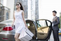 Chinese chauffeur opening car door for young woman — Stock Photo