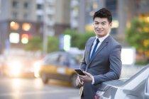 Empresário chinês de pé ao lado do carro com smartphone — Fotografia de Stock