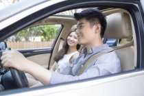 Chinese couple riding in car — Stock Photo