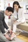 Cinese coppia acquisto scarpe in negozio — Foto stock
