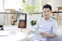 Homem chinês usando tablet digital no café — Fotografia de Stock