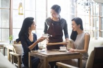 Chinese waitress serving coffee to female friends in cafe — Stock Photo