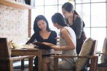 Chinesischen Freundinnen mit Kellnerin im Café bestellen — Stockfoto