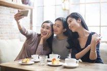 Chinesischen Freundinnen nehmen Selfie in Coffee-shop — Stockfoto