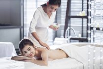 Young Chinese woman receiving massage at spa center — Stock Photo